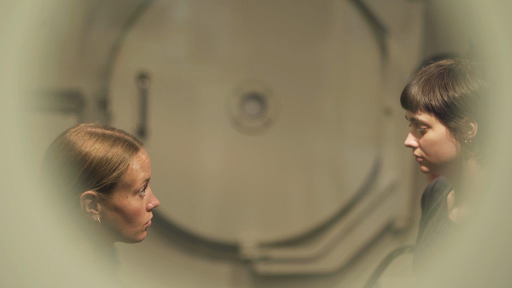 A film still of two white women in their late 20s facing one another, either side of the image. We're looking through a porthole, they're inside a hyperbaric chamber, which looks like a beige submarine or space shuttle inside. The woman on the left (Esther) is looking directly at the other woman with intent. She has blonde hair in a low pony and dark eyes. The woman on the right (Antonia) is looking slightly down, not ex