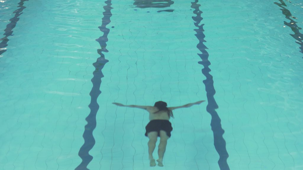 A film still of someone (Charlie) in a swimming pool, of which we can't see the edges. He's in the bottom centre of the image, under the water facing downwards, with legs straight behind him and his arms stretched out wide either side of him. He's a white man with long dark hair and dark swimming trunks.