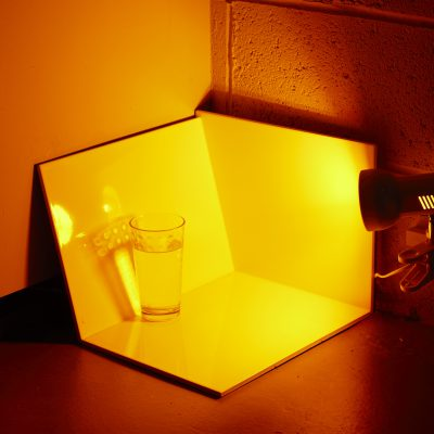 A small glass of water, mirrored surfaces surround it, and it's lit in an orange light.