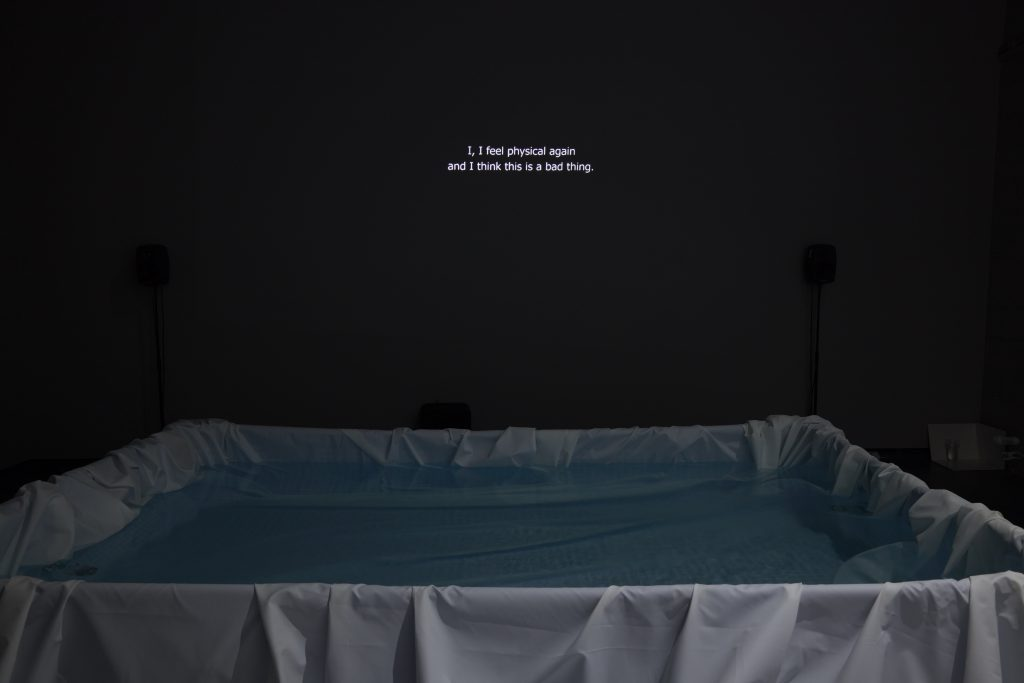 An image of a dark gallery space, a free standing pool draped in white fabric and full of water at the bottom of the image, and on the wall beyond it is the projected text: 'I, I feel physical again and I think this is a bad thing.'