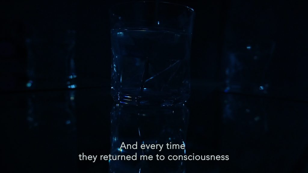 A small glass of water and vague reflections of it either side, in a very dark space. A subtitle reads: 'And every time they returned me to consciousness'