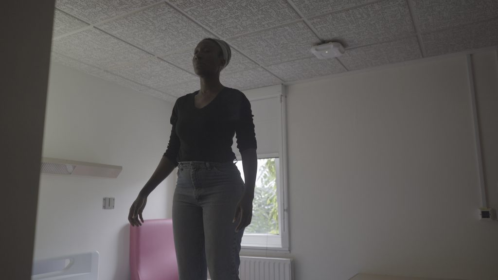 A film still of a black woman (Nephertiti) in her early 30s standing in a hospital bedroom. She has her eyes closed, her arms by her sides but with a little tension in her hands, looking focused but peaceful. We can tell she is standing on something because of her proximity to the ceiling. She's wearing a long sleeved black top, light blue jeans, and a grey headwrap. The interior is grey except for a pink chair by the window.